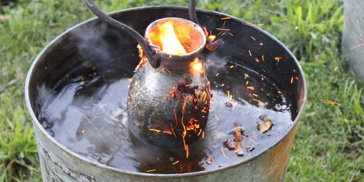 A glowing raku vase in flames being lowered into water with tongs