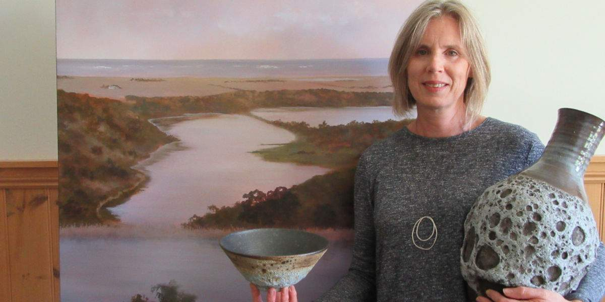 Judy Rauert holding a ceramic vase and bowl in front of a painting of Tower Hill
